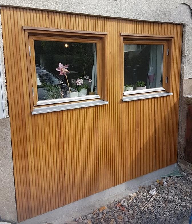 Tidigare satt här en garagedörr.Karrosseripanelen i furu har tillverkats av hyvleriet på Nacka trä. Känslan av ekpanel har vi fått genom Jotuns lasyr trebitt natur.